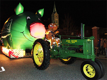 Bank of Washington employees dressed as Gingerbread Man driving a tractor pulling the big inflatable pig dressed as Rudolph for the 2015 Holiday Parade of Lights